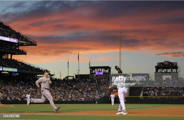 First baseman Todd Helton of the Colorado Rockies gets the put out on Buster Posey of the San Francisco Giants as he grounds out as the sun sets in...