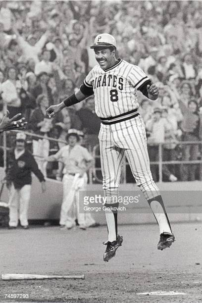 First baseman Willie Stargell of the Pittsburgh Pirates smiles and jumps in the air as he scores the winning run in a Major League Baseball game at...