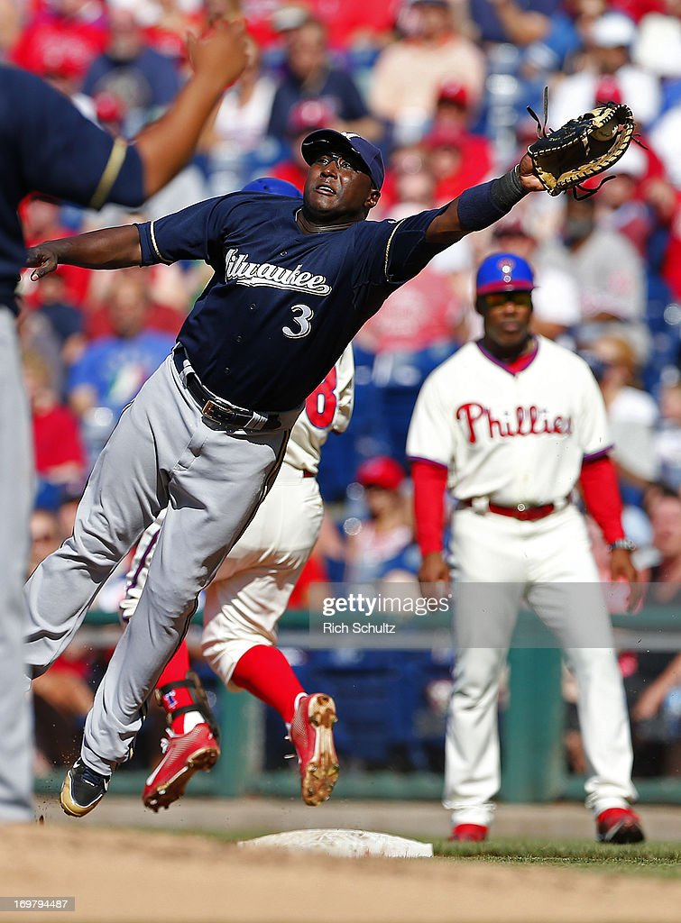 First baseman Yuniesky Betancourt of the Milwaukee Brewers reaches high for a throw as Kevin Frandsen of the Philadelphia Phillies beats it out for a...