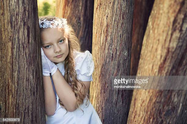 First communion girl (8-9) leaning against tree
