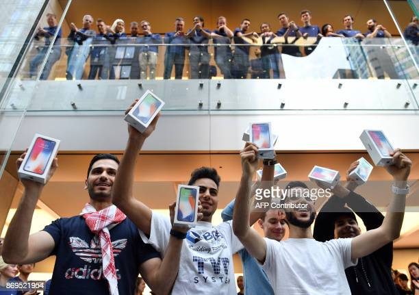 First customers display their iPhone X sets at an Apple showroom in Sydney on November 3 2017 Apple iPhone X went for sale in Australia with long...