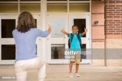 First day of school.  Little boy reaches out to mom.