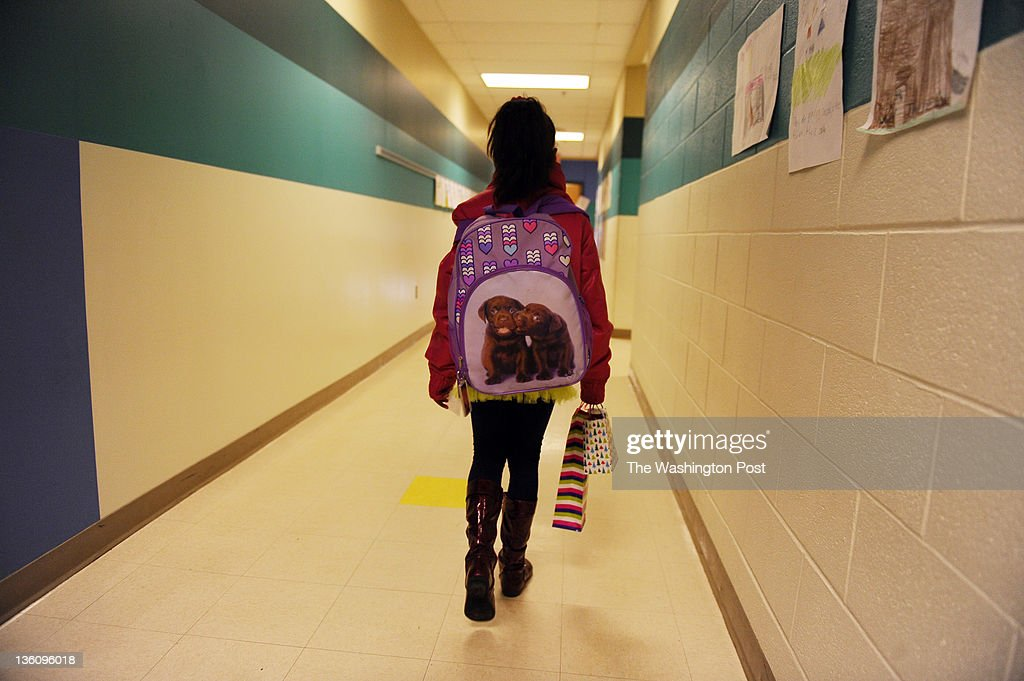 First grader Janae Harris walks down the hall with Christmas gifts for her teacher Kelly Grinham at Spark Matsunaga Elementary School on December 23...