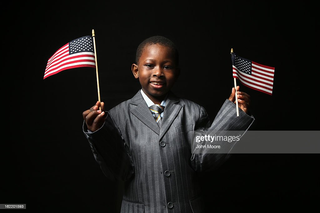 First grader Moussa Doucovre, 6, born in Senegal, waves flags given to him by the U.S. Citizenship and Immigration Services (USCIS), while waiting to receive his citizenship certificate on February 19, 2013 in New York City. His father, a naturalized American citizen, works in retail in the Bronx, New York City. Almost 300 foreign-born children of naturalized Americans received citizenship certificates Tuesday at the USCIS center during the special event. Children of naturalized immigrants receive U.S. citizenship if they arrive to the United States as minors, but they must go through a process at USCIS to receive official citizenship documents proving they have become Americans.