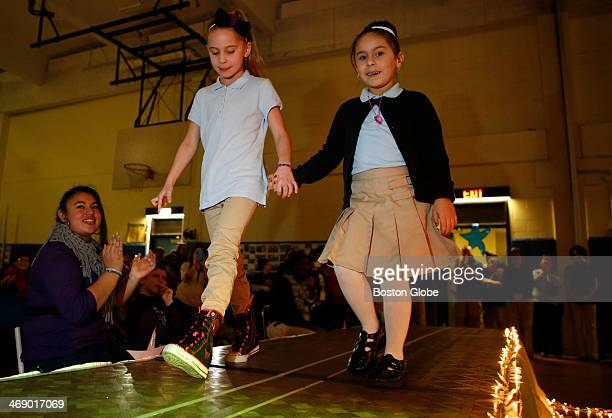 First grader Talia Schumanwalks down the runway with kindergartener Abigale Correia right during a school fashion show of new dress policy options...