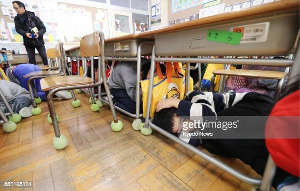 First graders at an elementary school in Morioka of northeastern Japan's Iwate Prefecture shelter under their desks in their classroom during an...
