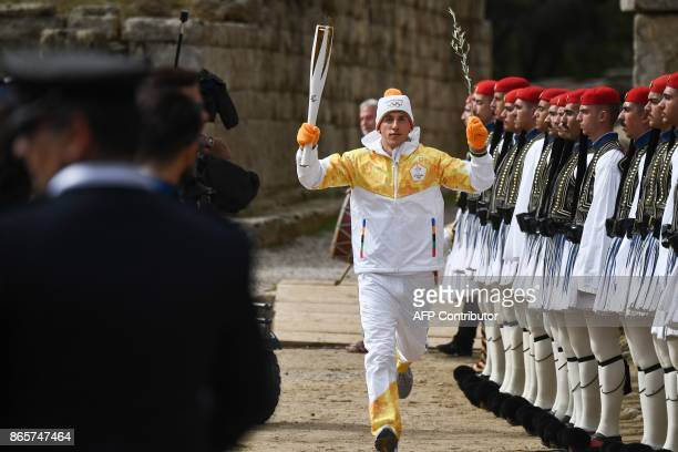 First Greek torchbearer for Pyeongchang 2018 crosscountry skier Apostolos Angelis holds the Olympic flame at the Temple of Hera on October 24 2017...
