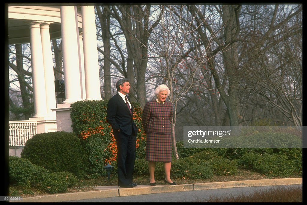 First Lady Barbara Bush chatting with CBS anchorman Dan Rather framed by verdant shrubbery & winter-bare trees, on White House grounds, January 11, 1989.