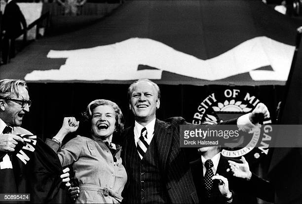 First Lady Betty Ford and American President Gerald Ford cheer at a rally held on the University of Michigan campus during Ford's reelection campaign...