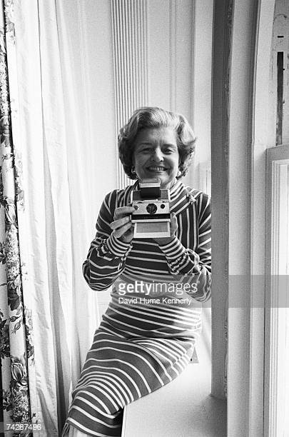 First Lady Betty Ford takes a Polaroid photograph of the official presidential photographer on the patio just outside the White House Oval Office on...