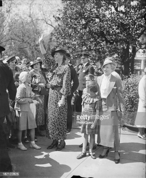 First Lady Eleanor Roosevelt waves as she hosts the the annual Easter egg rolling on the White House lawn Washington DC 1935 Among those picture with...