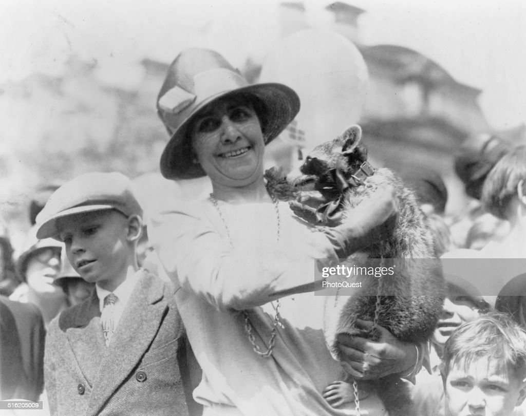 US First Lady Grace Coolidge holds up her pet raccoon Rebecca for a crowd of children at the annual White House Easter Egg Roll Washington DC April...