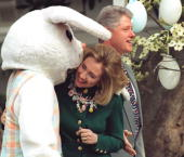 First Lady Hillary Clinton listens to the Easter Bunny whispering in her ear while President Bill Clinton stands by during the annual Easter Egg Roll...