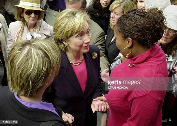 First Lady Hillary Rodham Clinton holds hands with Miss Wynder and Ann Payton Bryant 23 August on the steps of New York's City Hall after press...