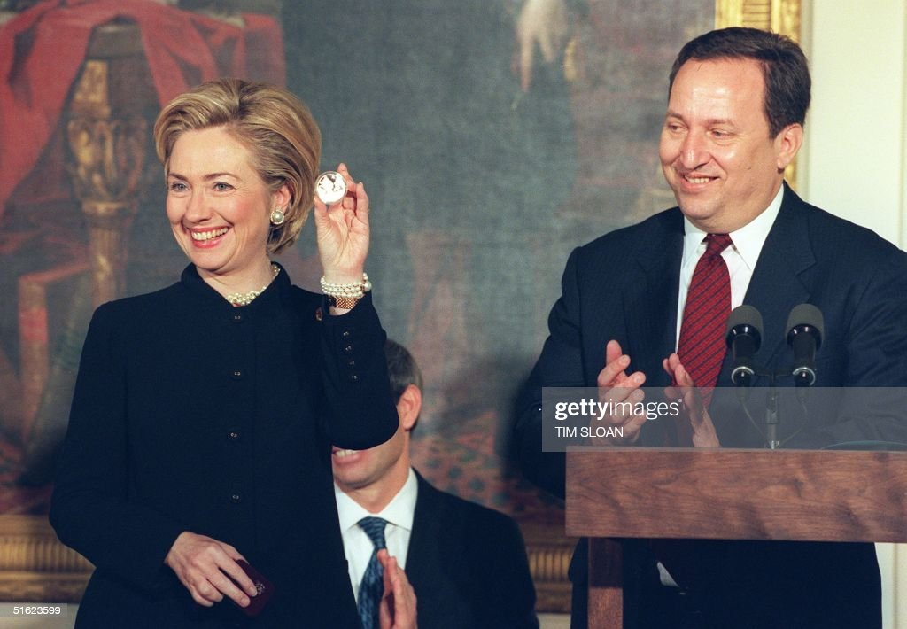 US First Lady Hillary Rodham Clinton (L) holds up the new Dolley Madison commemorative silver dollar coin as Deputy Secertary of the Treasury <a gi-track='captionPersonalityLinkClicked' href=/galleries/search?phrase=Lawrence+Summers&family=editorial&specificpeople=224698 ng-click='$event.stopPropagation()'>Lawrence Summers</a> (R) looks on during ceremonies 11 January at the White House in Washington, DC. The coin designed by Tiffany and Co., available at the US Mint, celebrates the life, achievements and 150th anniversary of Dolley Madison's death. Madison, wife of US President James Madison, was the first presidential wife to be called First Lady. AFP PHOTO/Tim SLOAN