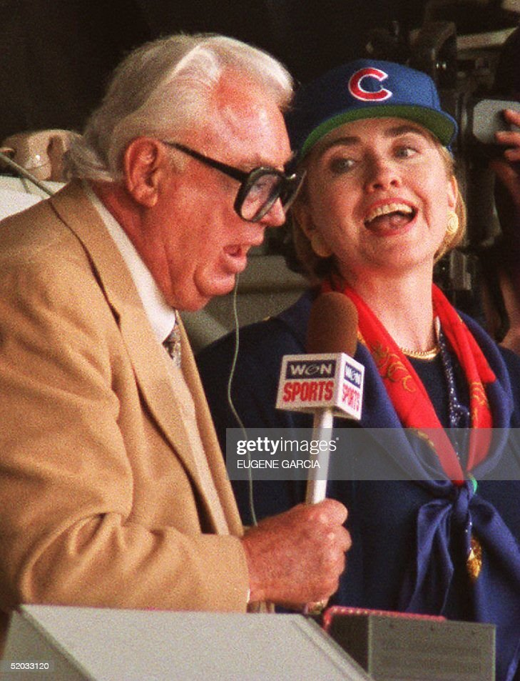 U.S. First Lady Hillary Rodham Clinton (R) sings 'Take Me Out to the Ballgame' with Chicago Cubs television announcer Harry Caray (L) 04 April during their game against the New York Mets in Chicago. Hillary Clinton also threw out the first pitch of the game.