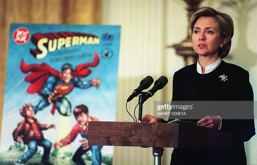 US First Lady Hillary Rodham Clinton unveils a Superman comic book for children in Kosovo to provide information on the dangers of landmines 02 August 1999 at the White House in Washington, DC. Similar comic books were produced and distributed in Bosnia and Central America. AFP PHOTO/Manny CENETA