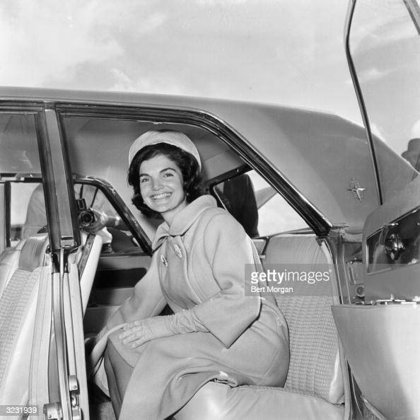 First Lady Jacqueline Kennedy sits in the back seat of a car and smiles while a photographer takes her picture Palm Beach Florida She is wearing a...