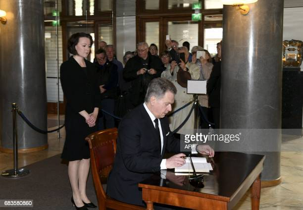 First lady Jenni Haukio looks on as President Sauli Niinisto signs the book of condolence for the late President of Finland Mauno Koivisto at the...
