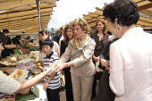 US First Lady Laura Bush examines local produce offered by a market trader as Sousa Uva wife of EU Commission Chairman Jose Manuel Barroso Sarah...