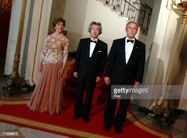 First lady Laura Bush Japanese Prime Minister Junichiro Koizumi and US President George W Bush pose in the Grand Foyer for a photo opportunity at the...