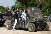 First Lady Laura Bush watches with friends from the comfort of a vehicle as former President George W Bush leads a pack of bicycle riders through his...