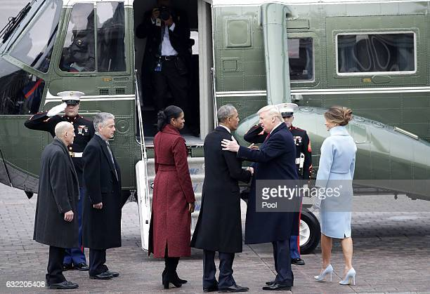 First Lady Melania Trump and former First Lady Michelle Obama watch Former President of the United States Barack Obama shakes hands with newly...