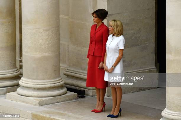 US First Lady Melania Trump and French president's wife Brigitte Macron stand during a welcome ceremony at Les Invalides in Paris on July 13 2017...