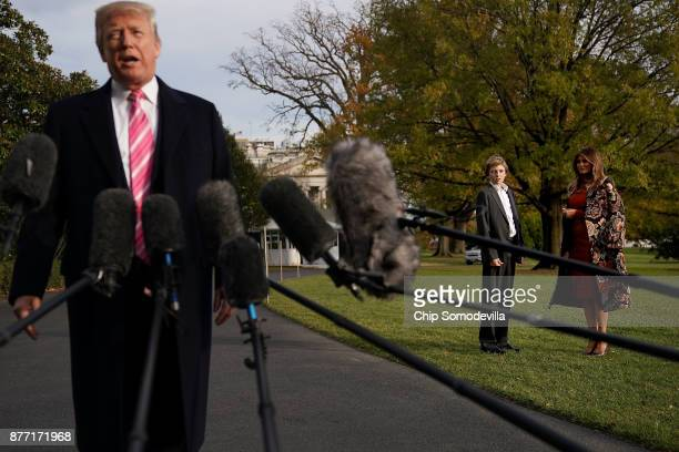 S first lady Melania Trump and her son Barron Trump listen to President Donald Trump as talks to reporters before they depart the White House...