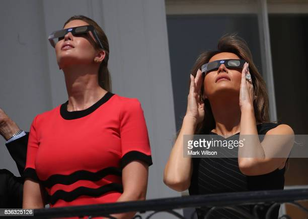 First lady Melania Trump and Ivanka Trump wear special glasses to view the solar eclipse at the White House on August 21 2017 in Washington DC...