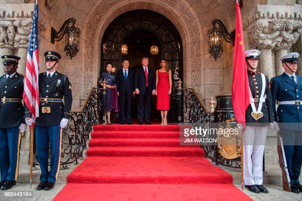 US First Lady Melania Trump and President Donald Trump pose with Chinese President Xi Jinping and his wife Peng Liyuan upon their arrival to the...
