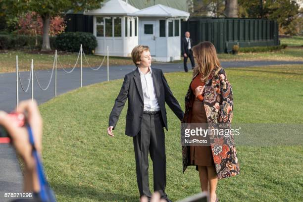 First Lady Melania Trump and son Barron wait for President Donald Trump as he speaks to reporters before their departure for the Thanksgiving Holiday...