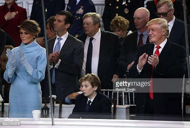 First lady Melania Trump Barron Trump and US President Donald Trump watch the Inaugural Parade from the main reviewing stand in front of the White...