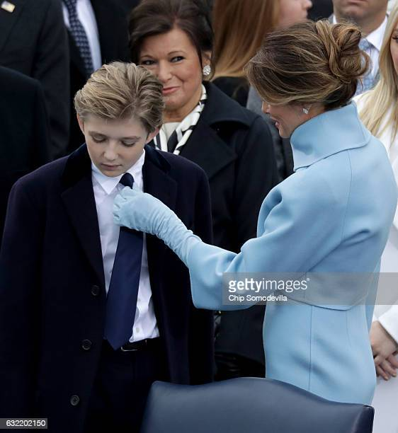 First lady Melania Trump fixes the tie of her son Barron Trump prior to US President Donald Trump's inaugural address on the West Front of the US...