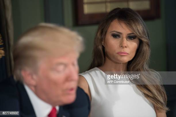 US First Lady Melania Trump listens to her husband President Donald Trump speak at a meeting with administration officials on the opioid addiction...
