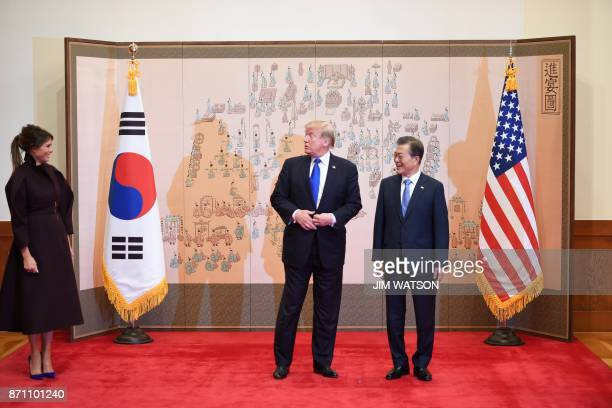 US First Lady Melania Trump looks at US President Donald Trump and South Korean President Moon JaeIn during their meeting at presidential Blue House...