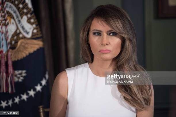 US First Lady Melania Trump looks on as her husband President Donald Trump speaks at a meeting with administration on the opioid addiction crisis at...