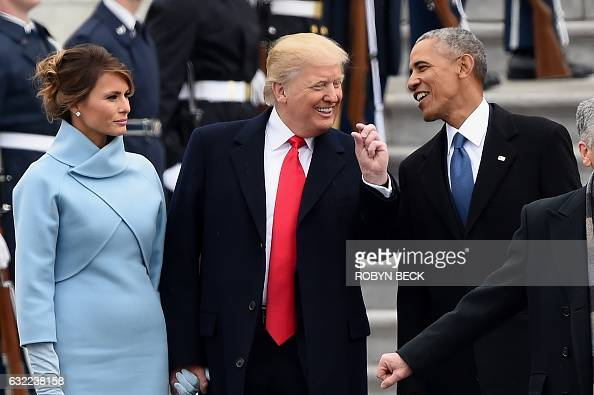 US First Lady Melania Trump looks on as US President Donald Trump and former President Barack Obama talk on the East front steps of the US Capitol...