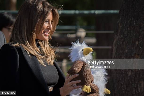 US First Lady Melania Trump offers stuffed toy eagles from the US to children at the Beijing Zoo in Beijing on November 10 2017 / AFP PHOTO / NICOLAS...