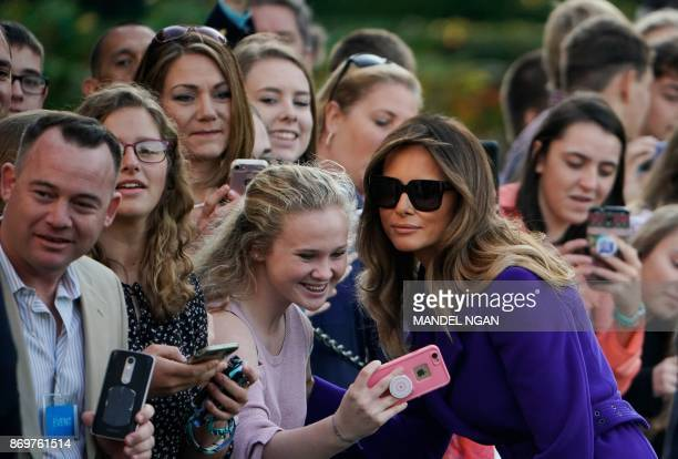 US First Lady Melania Trump poses for a photo with a guest as she and US President Donald Trump make their way to board Marine One before departing...