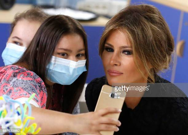 First Lady Melania Trump poses for a selfie with a young patient during a visit to the Pediatric Hospital Bambin Gesù on May 24 2017 in Rome After a...