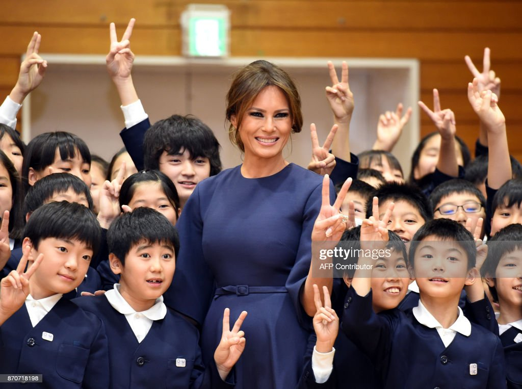 First Lady Melania Trump poses with 4th graders at the Kyobashi Tsukiji elementary school in Tokyo on November 6, 2017. President Donald Trump lashed out at the US trade relationship with Japan, saying it was 'not fair and open', as he prepared for formal talks with his Japanese counterpart. /