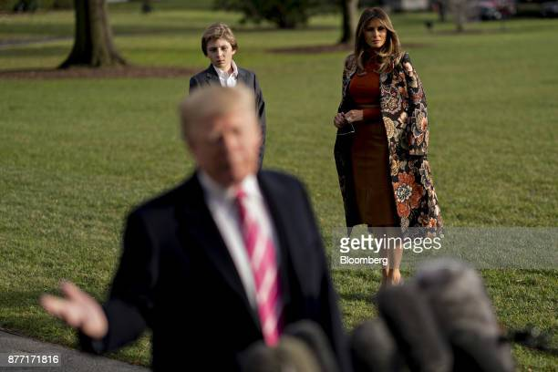 US First Lady Melania Trump right and son Barron Trump left stand on the South Lawn of the White House as US President Donald Trump speaks to members...