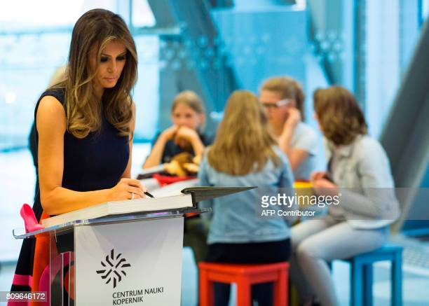 US First Lady Melania Trump signs the Golden Book as she visits the Copernicus Science Center with the Polish President's wife in Warsaw on July 6...