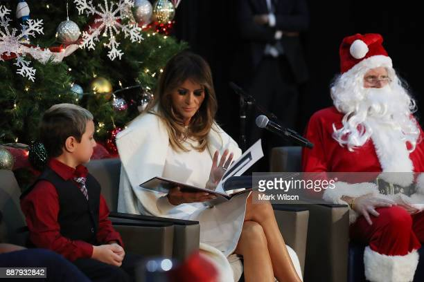 First lady Melania Trump sits between Damian Contreras and a person dressed as Santa Claus as she reads the Christmas book The Polar Express at...