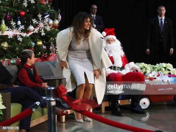 First lady Melania Trump sits Damian Contreras and a person dressed as Santa Claus after reading the Christmas book The Polar Express to children at...