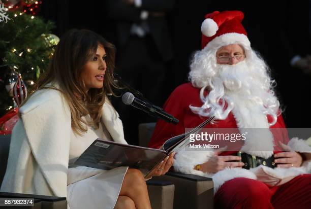 First lady Melania Trump sits next to a person dressed as Santa Claus as she reads the Christmas book The Polar Express to children at Children's...