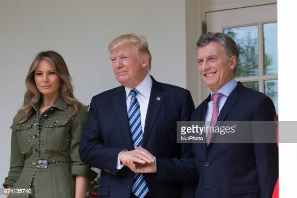 US First Lady Melania Trump smiles as President Donald Trump and Argentina's President Mauricio Macri shake hands in the West Wing Colonnade of the...