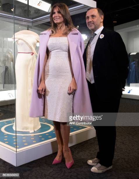 US First Lady Melania Trump stands alongside the gown she wore to the 2017 inaugural balls and the gown's designer Herve Pierre as she donates the...