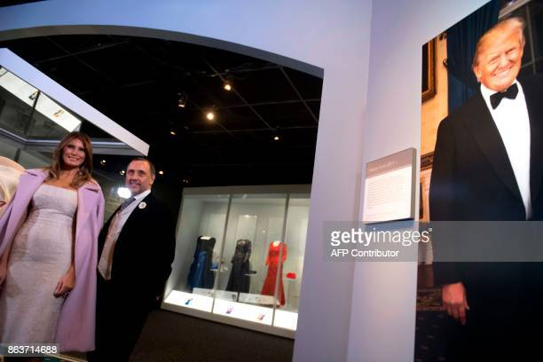 US First Lady Melania Trump stands alongside the gown she wore to the 2017 inaugural balls with the gown's designer Herve Pierre and a photograph of...